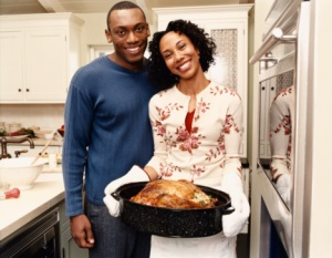 Portrait of a Couple Standing Side by Side in a Kitchen, with the Woman Proudly Holding a Roasting Dish Containing a Cooked Turkey